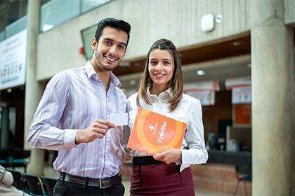 Hombre y mujer jóvenes con catálogo de crédito Compensar, Líneas de crédito compensar