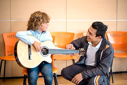 Niño aprendiendo a tocar guitarra con profesor de Compensar, Cursos de artes y manualidades en Compensar