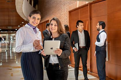Mujeres sonriendo frente al auditorio Compensar avenida 68 sede para eventos empresariales