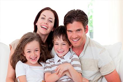 Familia sonriendo en primer plano, subsidio monetario Compensar