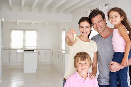 Familia sonriendo en la sala de su nueva casa, crédito para compra de vivienda Compensar